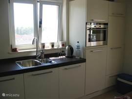 De andere zijde van de hoekkeuken. De keuken heeft een eettafel met 4 stoelen. Via de schuifpui kun je naar het overdekte terras met eettafel en 6 stoelen, met prachtig uitzicht.