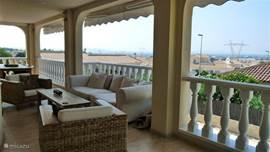 Het balkon met prachtig uitzicht. Op de voorgrond de luxe loungeset.  Het gehele balkon is tegen de zon te beschermen met 3 electrische zonneschermen.