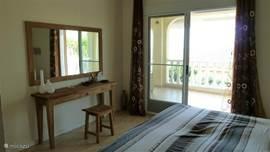 De masterbedroom is voorzien van kaptafel en spiegel en men kan vanuit deze slaapkamer via de schuifpui naar het overdekte balkon.