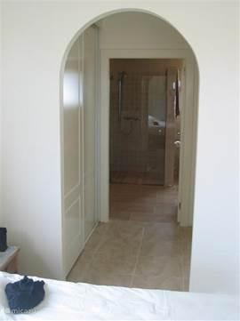 De doorloop naar de badkamer vanuit de masterbedroom. Links en rechts zijn grote wandkasten.
