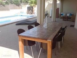 De eettafel buiten onder het overdekte terras van het gastenverblijf.  Direct te bereiken via de schuifdeuren vanuit de keuken.
