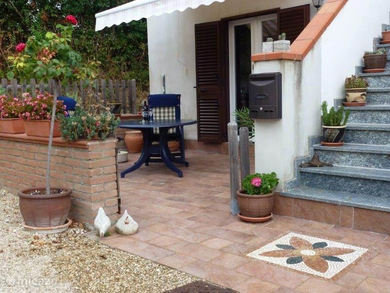 Het eigen zonnige terras voor het appartement met comfortabele verstelbare stoelen en kussens en een zonnescherm
