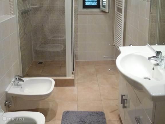 Ruime badkamer, met douche, wasmeubel, toilet en bidet. Handdoeken en haardroger zijn aanwezig. Raam met hor en luik.