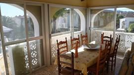 Een mooi ingeglaasd terras in Spaanse stijl, vanwaar U naar een groot buiten terras kunt waar een mooie zit/eethoek staat onder een mooie paty tent.