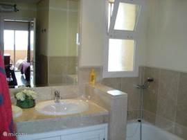 Ruime badkamer met dubbele wastafel, inloopdouche en ligbad.