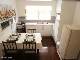 Keuken met eettafel, fornuis, koelkast, magnetron, koffiezetapparaat, ricecooker en waterkoker.