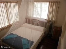 Tweepersoonskamer, met linnenkast, commode, ventilator. Ramen zijn voorzien van horren. Optioneel is een badlinnenset te huur (1 strandlaken, 3 baddoeken en 3 washandjes) per persoon per verblijf.