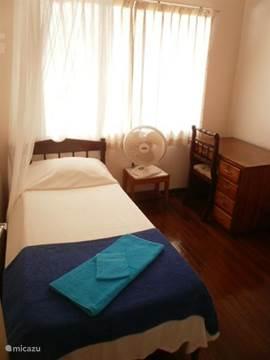 Eenpersoonskamer met kledingkast, bureau, ventilator. De ramen zijn voorzien van horren.