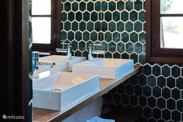 Badkamer met inloopdouche, twee wastafels en originele tegels uit Salernes