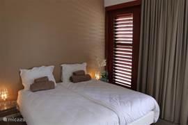 Master bedroom met eigen airco, balkon, ensuite-badkamer en inloopkast.