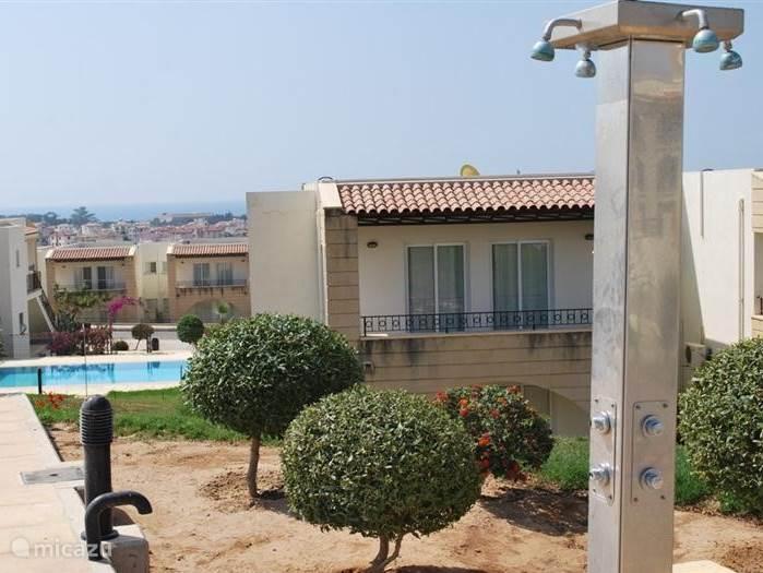 Achteraanzicht van het appartement op de eerste verdieping, met uitzicht over het grote zwembad van Hilltop Resort.