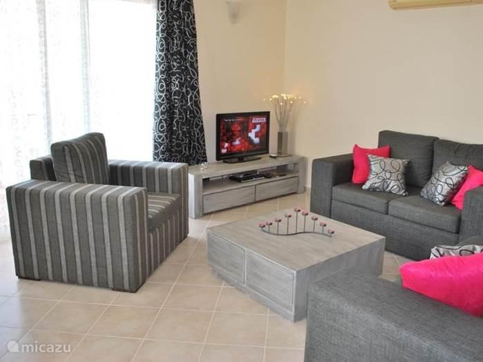 De zithoek: het appartement is in mei 2011 volledig nieuw ingericht. De zithoek bestaat uit een 2,5 zits bank (uit te klappen tot sofabed), een 2 zitsbank en een ruime fauteuil. Uiteraard is er een LCD televisie (32 inch) met DVD speler en een satellietontvanger met de Nederlandse zender BVN.
