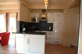 The fully equipped kitchen with ceramic hob, oven, microwave, dishwasher and fridge freezer