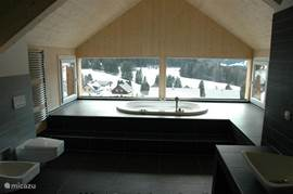 The luxurious bathroom with double rain shower and Jacuzzi overlooking the mountains.