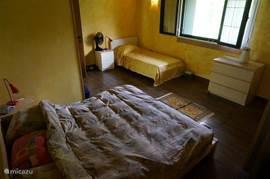 De ouderslaapkamer beschikt over een lits jemaux en een 1 persoonsbed in zijn eigen hoekje. Ook hier heeft elk bed zijn eigen nachtkastje en -lampje. Voor alle bedden zijn dekbedden (en dekens) aanwezig. Zowel in dons als in kunststofvezel.