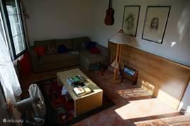Heerlijk lichte zitkamer, met 4/5 zits bank en losse fauteuil. Ook staat hier de boekenkast met, naast boeken in diverse genre's, ook spelletjes en films op dvd.