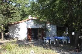 De achterzijde van het huis met een terras waar men desgewenst gezellig buiten kunt ontbijten, lunchen of dineren.