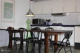 Open keuken met gezellige eethoek, twee koelkasten, 4-pits elektrische kookmogelijkheden en wasmachine.