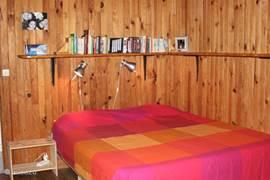 Tweepersoons slaapkamer met houten vloeren en wanden. Tevens mooi uitzicht vanuit het raam.