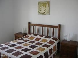 Een tweepersoons slaapkamer met openslaande deuren naar het overdekte terras, airconditioning (verwarmen en koelen), inbouwkasten en een kaptafel met spiegel.
