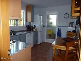 Complete keuken royaal voorzien van servies etc.etc. daarachter bijkeuken met wasmachine en  tweede deur naar het terras