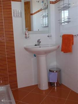 De doucheruimte met toilet op de benedenverdieping waar ook de woonkamer, de keuken en het terras bevindt