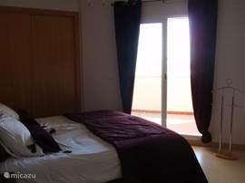 Dezelfde slaapkamer als de vorige foto maar dan met zicht op de schuifdeur van het terras. De zon schijnt ... wat gaan we vandaag doen?