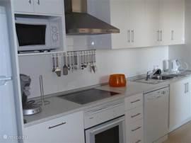 De keuken met magnetron, oven, koel/vrieskast, Senseo koffiezetapparaat, tosti-apparaat, keramische kookplaat, waterkoker, blender en electrische grillplaat