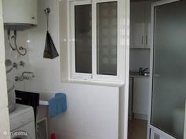 De bijkeuken grenzend aan de keuken met wasmachine en wasdroger.