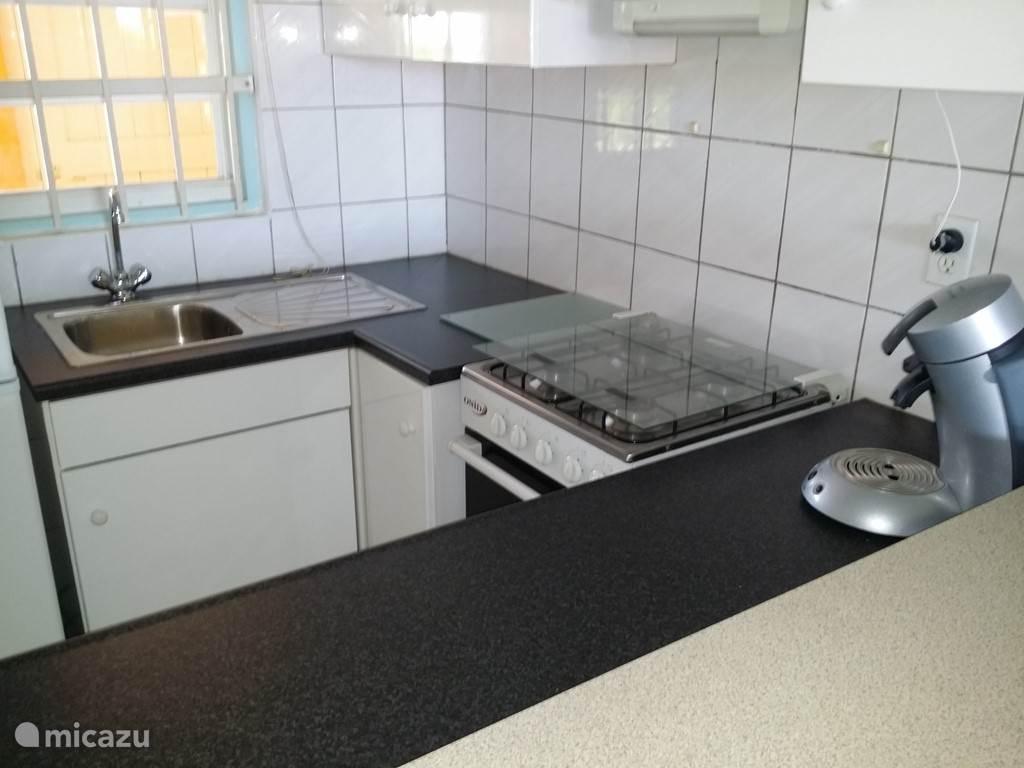 Keuken koelkast staat naast de spoelbak.
