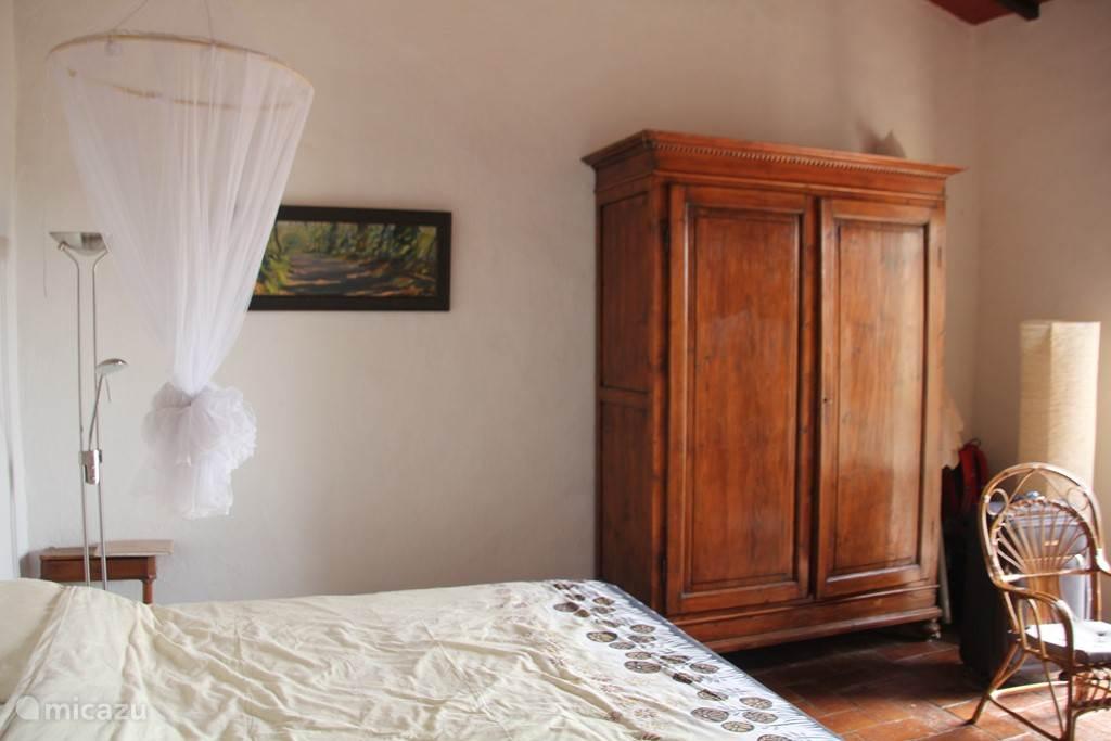 Zeer ruime eerste (2 persoons)slaapkamer in authentieke Toscaanse stijl, met openslaande deuren met fantastisch uitzicht over de glooiende Toscaanse heuvels. In de slaapkamer blijft het lekker koel.