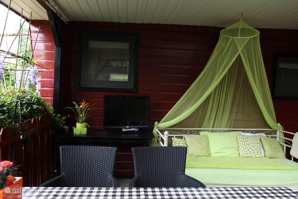 Een buitenbed met klamboe, een tv en een royale tafel met stoelen maken het tot een waar feestje om buiten te zitten.