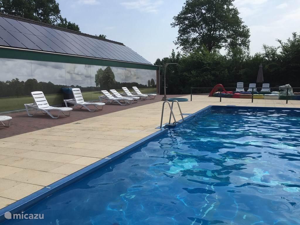 Het gezamenlijke verwarmde buiten zwembad op het park met ligbedden en ernaast is een overdekte kleine speelhal, beiden zijn zonder extra kosten te gebruiken.
