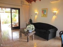 De woon/zitkamer met openslaande deuren naar het terras en zicht op de tropische tuin.