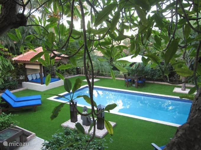 Uitzicht op het zwembad met gezellige zitje's en voldoende ruimte en schaduw om een rustige middag te hebben.