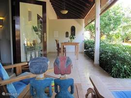 The terrace with comfortable chairs, dining table and a view of the tropical garden and pool.