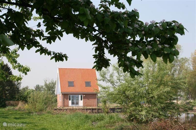 Zicht op het huisje vanaf de boomgaard