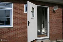 De deur is speciaal voor ons huisje gemaakt en voorzien van een authentiek rooster en raampje. Meteen rechts bevinden zich de trappen naar de verdieping en naar de kelder.