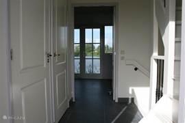 Bij binnenkomst in de hal wordt meteen duidelijk hoe mooi het zicht op het trekgat is. Links de deuren van het toilet en de meter- c.q. werkkast.
