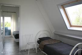 Bij aankomst op de verdieping kom je op de overloop, een ouderwetse benaming, voor de open ruimte met 2 slaapplaatsen. Een bed vast opgesteld en 1 bed daaronder geschoven. In deze ruimte bevindt zich ook de doorgang naar de slaapkamer met grote inbouwkast.