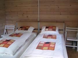 Slaapkamer met twee éénpersoonsbedden (2.10m) in het bijgebouw met eigen douche en toilet.