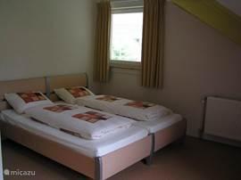 Bovenverdieping: 2 ruime slaapkamers met elk twee éénpersoonsbedden (2.10m). 1 slaapkamer heeft een ruim balkon en uitzicht op de tuin.
