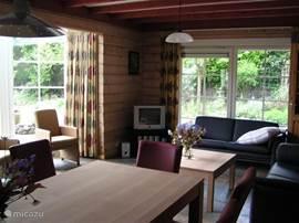 Een ruime gezellige woonkamer met een prachtige erker die uitzicht biedt op de kleurrijke tuin met grote vijver.