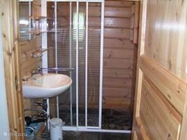 Ruime douche met wastafel. Toilet in de gang.
