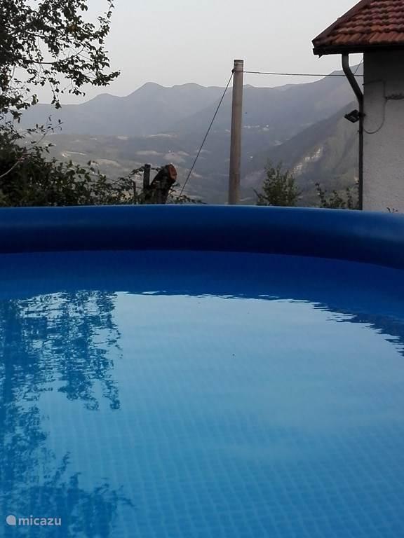 In het zwembad met uitzicht op de bergen.
