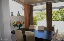De eethoek bevindt zich direkt achter de keuken met schuifdeuren naar het achterterras