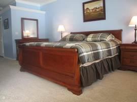 Masterbedroom (ouderslaapkamer)met een king bed, nachtkastjes, ladenkast met een spiegel en een hogere ladenkast met een tv, een inloopkast. Uit de masterbedroom de deur naar de grote badkamer met een bad, douche, wc, dubbele wasbak