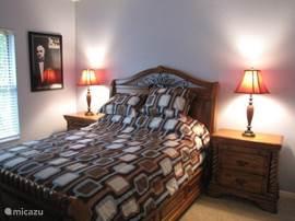 Tweede slaapkamer met een queen bed, nachtkastjes, een ladenkast met spiegel, tv en een inloopkast