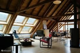 Het adembenemende hoge plafond met prachtige oude houten balken, de roterende open haard, het schitterende natuurlijke licht en het overdekte balkon met vrij uitzicht over de dramatische toppen van het massief Belledonne, zorgen voor een unieke beleving.