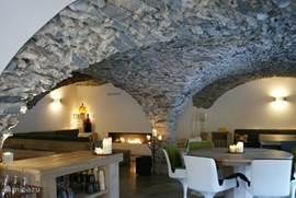 Op de begane grond vindt u het prachtige en stijlvol ingerichte gemeenschappelijke verblijf, dat          's avonds wordt omgetoverd tot een sfeervolle, met kerslicht gevulde, eetkamer. Het gewelfde natuur stenen plafond, de openhaard en het persoonlijk ontworpen meubilair zorgen voor een wow effect